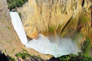 cachoeira com arco-íris em pedra amarela foto