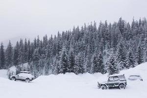 carro nas montanhas no fundo de uma floresta coberta de neve foto
