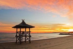 lindo pôr do sol na praia e cabana de praia foto