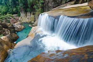 Cachoeira da selva com água corrente, pedras grandes