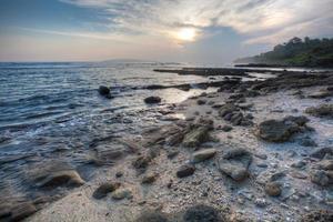 pôr do sol e céu azul na praia de Karapyak na Indonésia