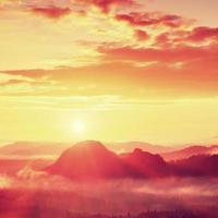 amanhecer enevoado vermelho. manhã nublada de outono em belas colinas. foto