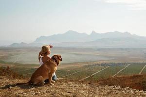 linda garota com cachorro no topo da montanha