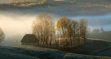 pequena cabana nas montanhas na névoa da manhã