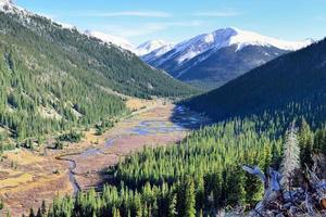montanhas e árvores cobertas de neve durante a temporada de folhagem foto