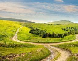 estrada transversal em prado encosta na montanha ao nascer do sol