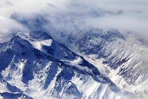 vista superior em montanhas de neve e geleira na névoa