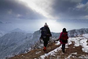 dois caminhantes caminhando no caminho do penhasco. foto