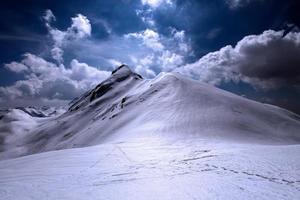 topo de montanha com neve e brilhante com pegadas em primeiro plano foto