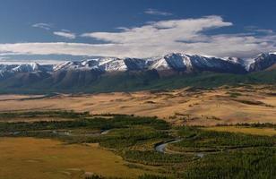 montanhas com picos nevados asiáticos nos meandros do rio ao fundo
