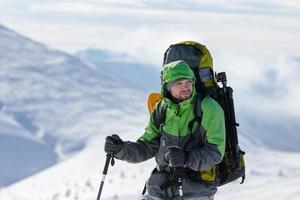mochileiro posando em montanhas de inverno