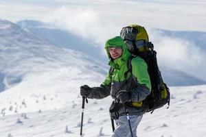 homem mochileiro caminhando nas montanhas de inverno em dia ensolarado