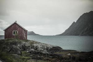 lofoten noruega vista para o mar do penhasco com pequena casa vermelha 2