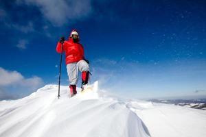 caminhante nas montanhas de inverno com raquetes de neve foto