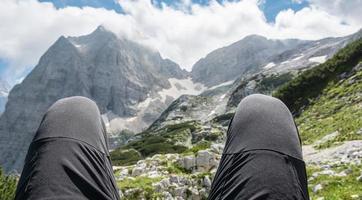 par de pernas com vista para a montanha foto