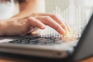 mão feminina usando teclado com gráfico financeiro