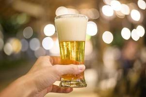 feche a mão segurando um copo de cerveja para comemorar foto
