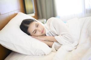 bela jovem dormindo em sua cama em casa foto