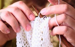 mulher com as mãos tricotando