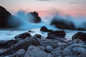 surfe à noite no oceano em uma costa rochosa