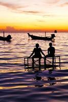 barco ao nascer do sol e água na costa sul da tailândia