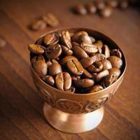 grãos de café em xícara de cobre foto