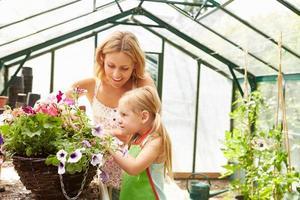 mãe e filha cultivando plantas em estufa