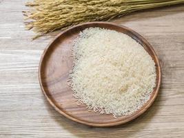 arroz branco na placa de madeira e planta de arroz foto