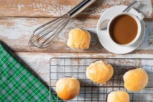 cupcakes frescos e café na mesa de madeira foto