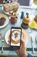 pessoa fotografando café da manhã