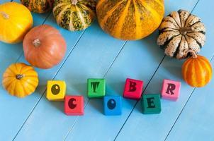 palavra outubro sobre cubos de brinquedos infantis e colheita de outono foto