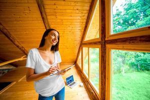 mulher com tablet na casa de madeira foto