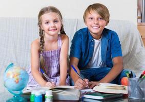 menino e irmã estudando com livros foto