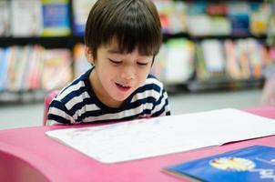 garotinho na biblioteca lendo livro