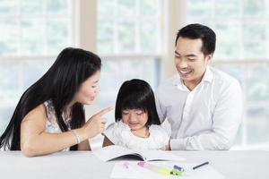 mãe repreendendo seu filho por fazer tarefa escolar