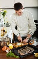 homem cozinhando truta peixe
