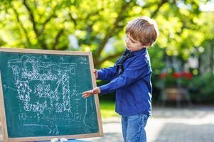 garotinho no quadro-negro fazendo apresentação