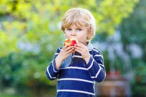 garoto loiro engraçado comendo maçã saudável foto