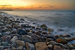 pôr do sol sobre praia de seixos