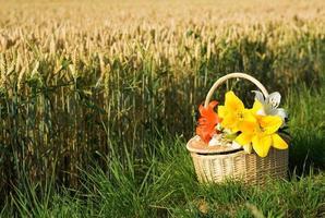 cesta de piquenique com ramo de flores