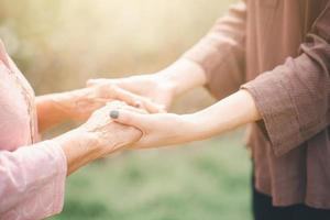 velha e jovem de mãos dadas