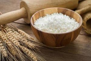 farinha na tigela e trigo na mesa de madeira