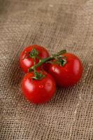 três tomates cereja molhados em tecido de juta foto