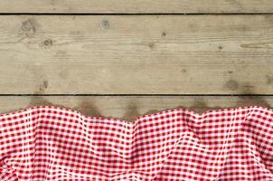 toalha de mesa dobrada vermelha sobre mesa de madeira