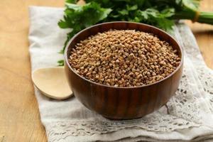 Sêmola de trigo sarraceno cru em uma tigela de madeira na mesa foto