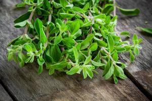 monte de manjerona de erva verde crua em uma mesa de madeira foto