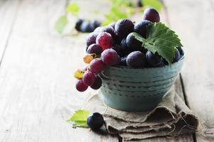 uva doce vermelha na mesa de madeira foto