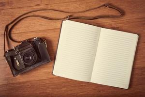 câmera vintage e diário na mesa de madeira.