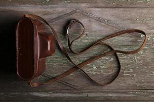 fundo de madeira com câmera fotográfica retro no estojo