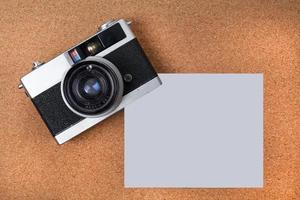 câmera vintage e papel de nota no fundo do quadro de cortiça